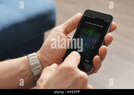 Kiev, Ukraine - March 06, 2016: A man hand holding the Apple iPhone 6 and enter passcode. The cellular phone is - Stock Photo