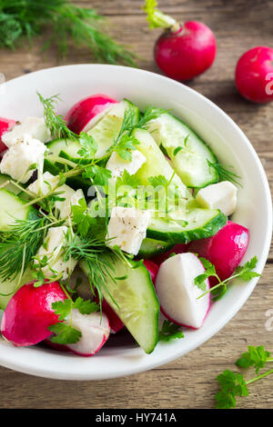 Spring vegetable salad with fresh cucumber, radishes, feta cheese, herbs, sprouts in bowl on wooden background  - Stock Photo