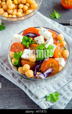 Chickpea and veggie salad with tomatoes, red cabbage, feta cheese (tofu) - healthy homemade vegan vegetarian diet - Stock Photo
