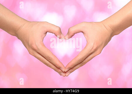 Shape of the heart made by male hands on pink heart bokeh background - Stock Photo