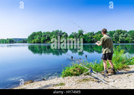 Fishing adventures, carp fishing. Angler is fishing with carpfishing technique in freshwater, in a beautiful summer - Stock Photo