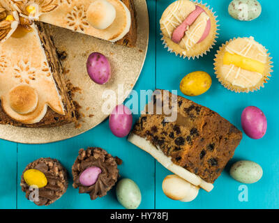 Traditional Easter Sunday Afternoon Tea and Cakes Against a Blue Background - Stock Photo