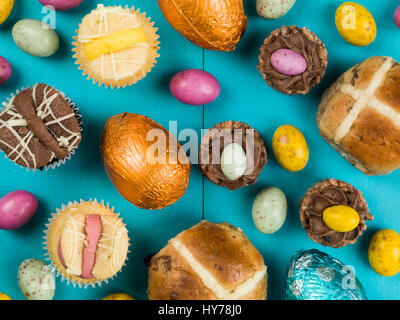 Selection of Traditional Easter Cakes and Mini Chocolate Easter Eggs Against a Blue Background - Stock Photo