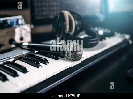 Professional music studio equipment, closeup. Musical keyboard, microphone and headphones. Audio recording tools - Stock Photo