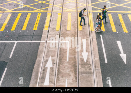 Hong Kong, China - 7 April 2015: Top view of people crossing a street - Stock Photo