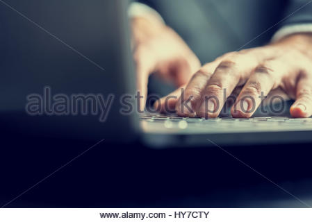 Low angle view from the back of the computer of a businessman typing on a laptop computer keyboard in a retro vintage - Stock Photo