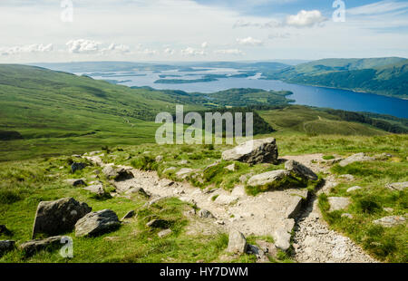 Path leading to the top of Ben Lomond in a sunny  day. Loch Lomond in the background. Scotland (UK). - Stock Photo
