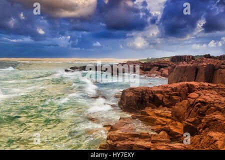 Rugged rocky coast transitioning to sand dunes and beach at stormy sunrise near Port Stephens, NSW, Australia. - Stock Photo