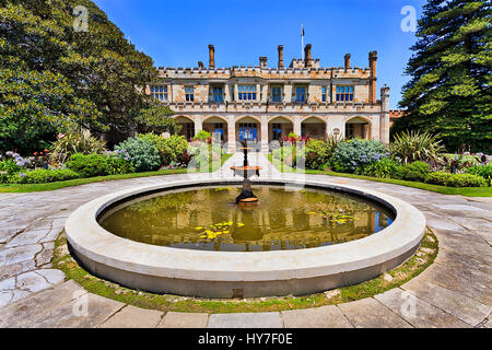 Colourful sunny summer day in Royal Botanic garden of Sydney with fountain and view on historic colonial palace - Stock Photo