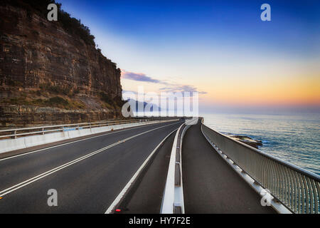 Sea cliff bridge around clifton cliff on Grand Pacific Drive in NSW, Australia, at sunset towards open ocean horizon. - Stock Photo