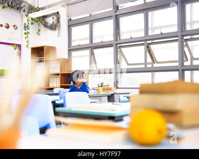 lonely asian elementary school child looking out of window thinking. - Stock Photo