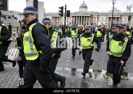 London, UK. 1st April, 2017. Police officers rush from Trafalgar Square to Whitehall towards supporters of anti - Stock Photo