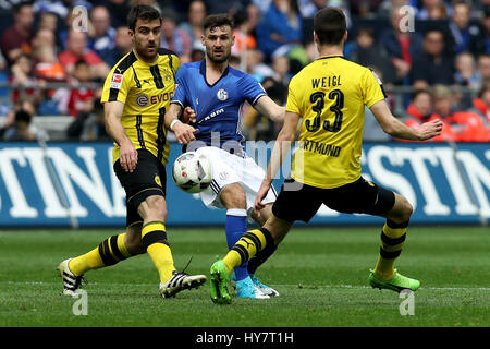 Gelsenkirchen. 1st Apr, 2017. Daniel Caligiuri (C) of FC Schalke 04 vies with Papastathopoulos Sokratis (L) and - Stock Photo