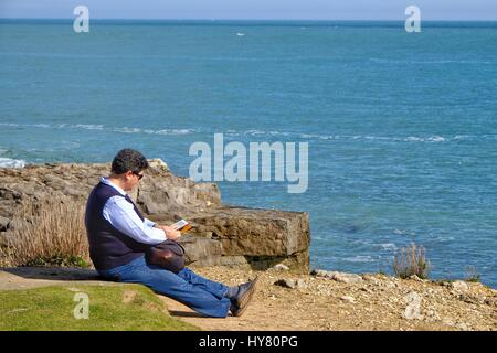 Portland Bill, Dorset, UK. 2nd Apr, 2017. A visitor reads and enjoyes the sunshine as people flock to Portland Bill - Stock Photo