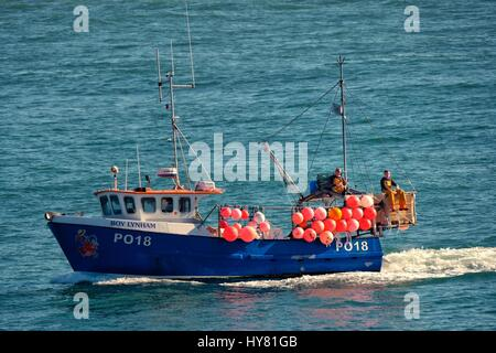 Portland Bill, Dorset, UK. 2nd Apr, 2017. Fishermen relax and soak in the sun as their fishing boat passes Portland - Stock Photo