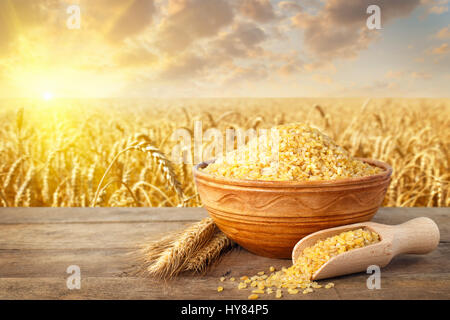 Bulgur or couscous in ceramic bowl and ears of wheat on table with ripe cereal field on the background. Agriculture - Stock Photo
