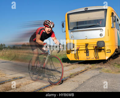 Terrified cyclist is rushing before by train on the tracks. Shocked biker ride a railway crossing in front of an - Stock Photo