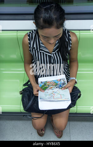 Asian tourist looks at the maps in the subway. A woman reading urban transport plan. Girl goes by train and studying - Stock Photo