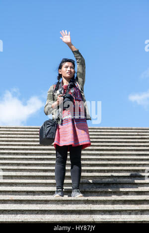 A young woman tourist with a camera standing on the stairs and waving hands. Girl traveler on the stairs with a - Stock Photo