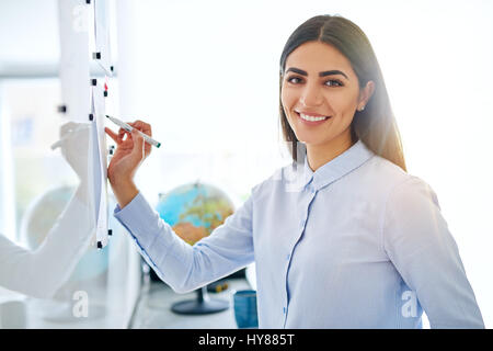 Gorgeous single young female business woman or instructor holding an erasable marker in hand at white board - Stock Photo