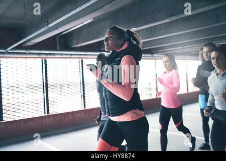 Attractive athletic woman urban running with a group of diverse young friends sprinting through a commercial undercover - Stock Photo