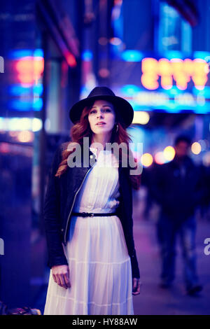 Young women in white dress and hat standing outside Radio City New York at dusk - Stock Photo