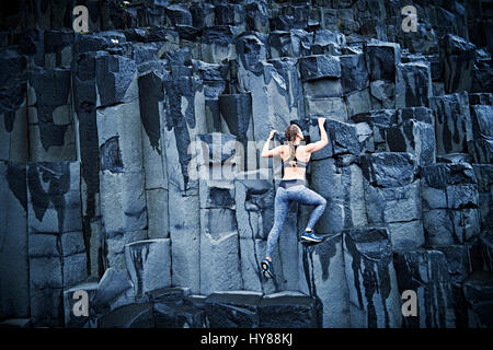 Happy confident young women climbing on basalt rock in southern Iceland - Stock Photo