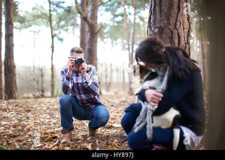 A man takes a photo of his female companion and her dog as they walk in the woods
