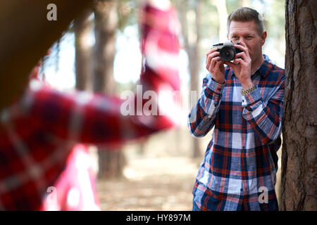 A man takes a photo of his female companion as they walk in the woods