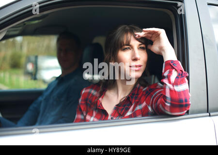 A woman looks wistfully out of a car window - Stock Photo