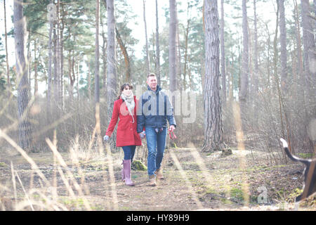 A young couple walk their dogs in the woods - Stock Photo