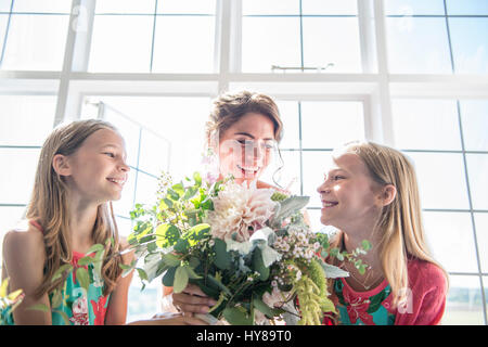 A bride with her twin bridesmaids holding a bouquet of flowers prior to her wedding - Stock Photo