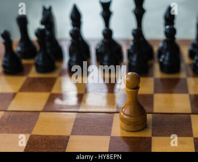 White chess pawn alone on a chessboard. conceptual photo of fighting alone and overcome the life difficulties alone. - Stock Photo