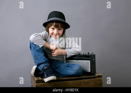 Cute boy with black hat, sitting on a wooden tray, holding old retro radio, smiling, isolated on gray background - Stock Photo