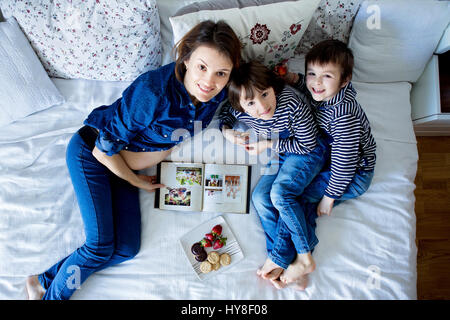 Beautiful mom and two children, boys, lying on the bed, eating strawberries and cookies, looking at camera, shot - Stock Photo