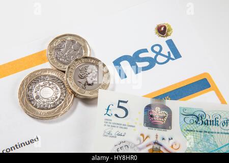 New £1 pound coins, £2 pound coins and £5 pound notes on an Premium Bond document - Stock Photo