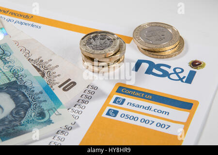 New £1 pound coins, £2 pound coins and £5 pound notes on a Premium Bond NS&I document - Stock Photo