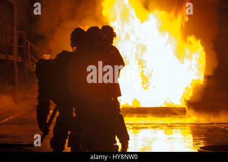 Group of firefighters in front of burning tank during firefighting exercise - Stock Photo
