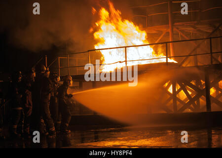Firefighters hosing down burning structure during firefighting exercise - Stock Photo
