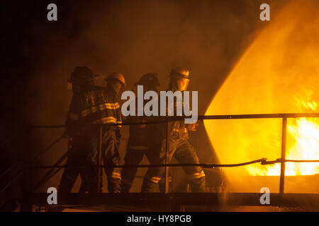 Firefighters using full spray to put out fire during firefighting exercise - Stock Photo