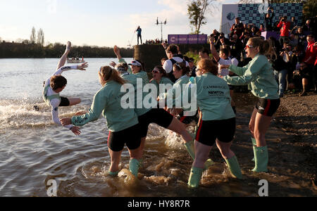 Cambridge Women's Matthew Holland (left) is thrown into the water after the Women's Boat Race on the River Thames, - Stock Photo
