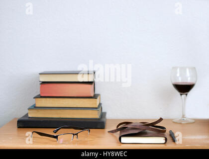 Leather journal, pencil, readers, and hardbound books stacked, used books on a weathered, used wooden desk, against - Stock Photo