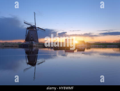 Silhouette of windmills at sunrise in Kinderdijk, Netherlands. Rustic landscape with traditional dutch windmills - Stock Photo