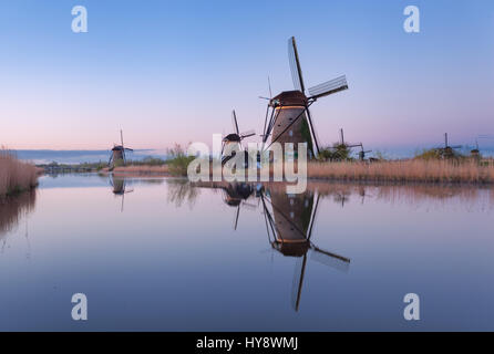Windmills and clear blue sky at sunrise in Kinderdijk, Netherlands. Spring rustic landscape with traditional dutch - Stock Photo