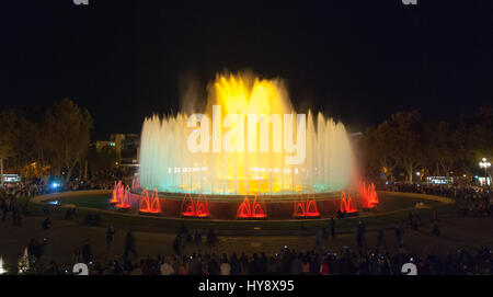 People attend colourful light & water fountain show.  Night at the Magic Fountain in Barcelona. Attraction turns - Stock Photo