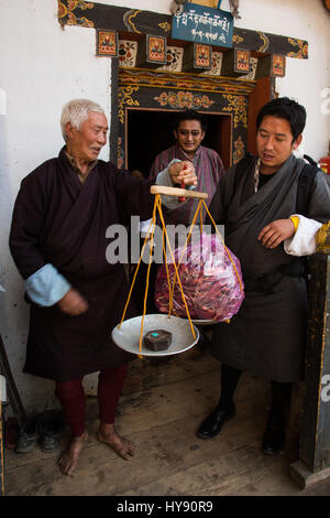 A young man buying peppers from an old farmer in traditional Bhutanese dress.  Tamchog, Bhutan. - Stock Photo
