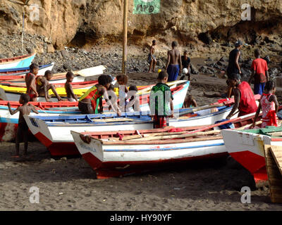 Children play on colorful fishing boats on shore in Cidade Velha on the island of Santiago, Cabo Verde or Cape Verde. - Stock Photo