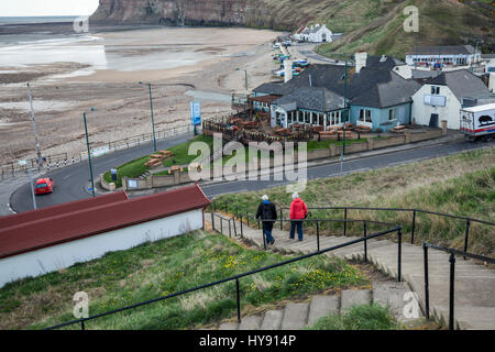 A mature man and woman walking down the steps to the beach area at Saltburn,England,UK - Stock Photo