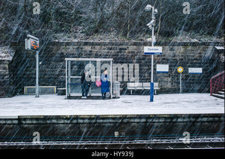 Two people waiting for a train in the snow. - Stock Photo