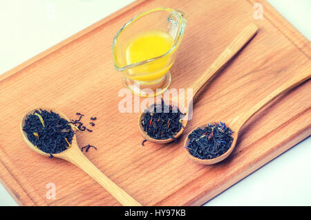 Black tea with herbs in wooden spoons with a glass container with honey on a wooden board. - Stock Photo